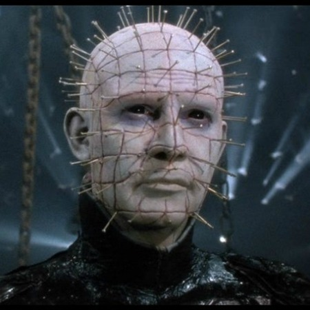 Pinhead wears black leather and stands in front of chains in a still from Hellbound: Hellraiser II.