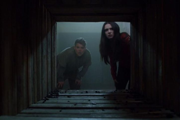 Image: A young woman with pale skin and long dark hair and a young man with light skin and blonde hair face the viewer as they peer down a dark tunnel.