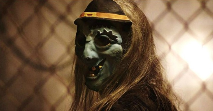 Image: A person with long blonde hair and a green witch mask looks over their shoulder at the viewer with a chain-link fence in the background.