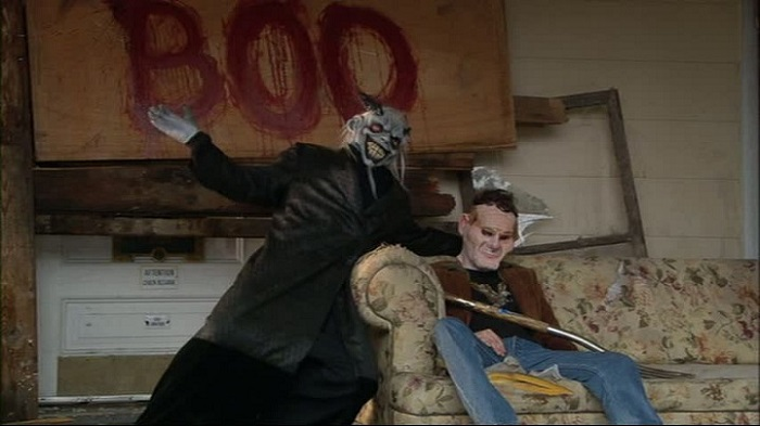 Image: A man in a devil costume poses next to a man slumped over on a couch. A bloody sign reading