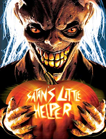 "Image: A grinning demonic figure holds a jack-o'-lantern with the words ""SATAN'S LITTLE HELPER"" carved into it."