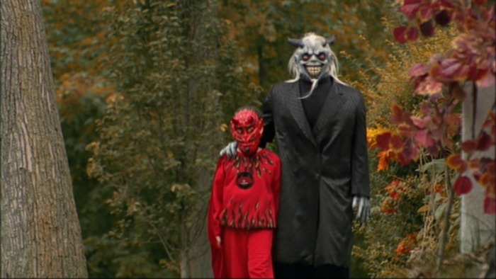 Image: A little boy in a red devil costume and a man in a pale demon mask and black coat walk down a street with trees and foliage surrounding them.
