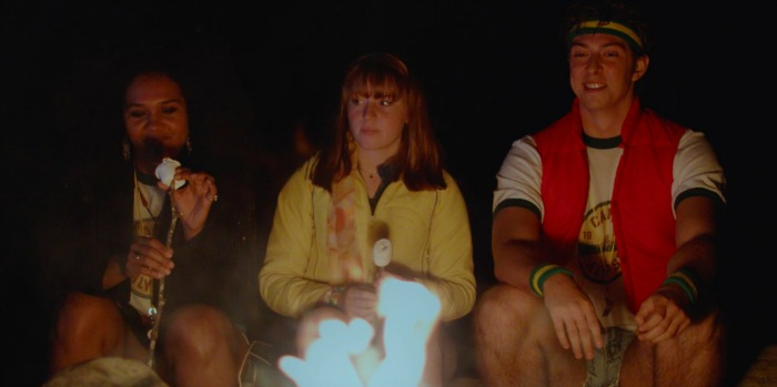 Three campers sit in front of a campfire. A Black woman in a jacket puts a marshmallow on a stick while a white woman with a yellow shirt and a white man with a red vest look on.