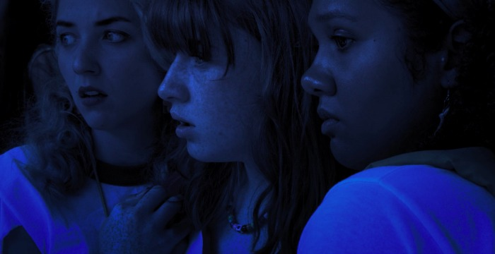 Image: A nighttime image of three women in profile looking off into the distance with concerned looks on their faces.