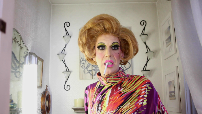 Image: A drag queen wearing a brightly colored caftan stares off camera with a cigarette dangling out of her mouth. She sits in front of a white wall with spare white decorations.