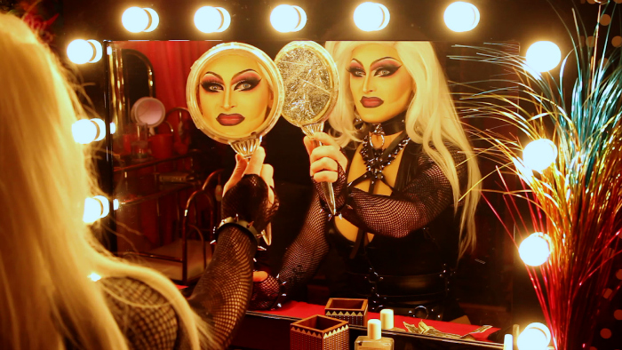 Image: A drag queen in a blonde wig and black bondage gear sits at a mirror surrounded by lights and holds a mirror in her hand. Her image in the handheld mirror makes eye contact with the viewer.