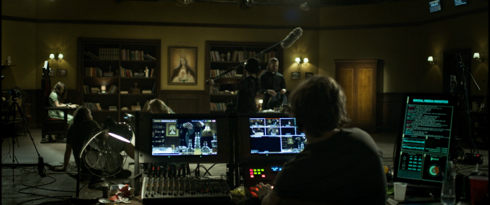 Image: A person sits at a control station with multiple screens. In the background, actors and crew members mill around on a set that looks like a priest's office.