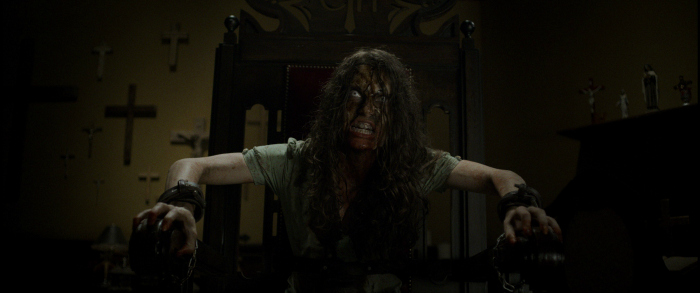 Image: A woman with a dirty, bloody face sneers off camera. She sits in a large chair with her wrists tied to the arms and crosses cover the wall behind her.