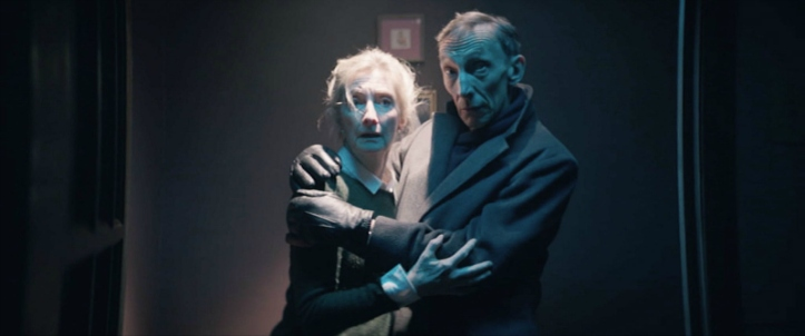 Image: A man in a dark coat holds a blonde woman in his arms. Both look alarmed.