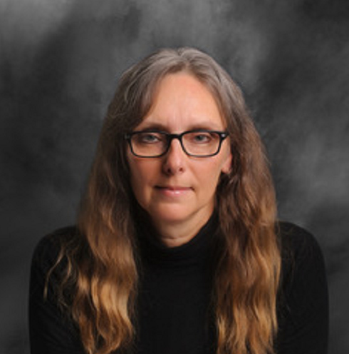 Image: A white woman with brown hair, black glasses, and a black sweater faces the camera in front of a grey and white backdrop.