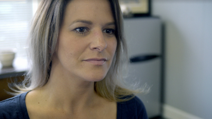 A woman with shoulder-length hair and a blue shirt sits in an office and looks at someone off-camera.