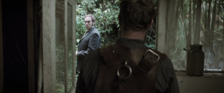 A man in a suit stands outside in front of overgrown trees. He looks over his shoulder into a dilapidated house where a man stands facing him. The man in the house wears a leather harness with straps and chains.