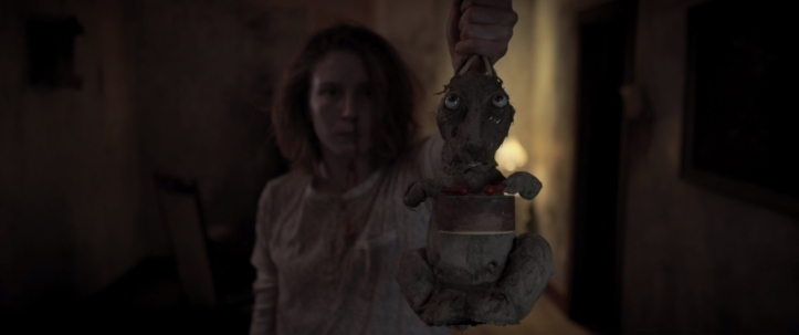 A woman with a pale shirt and a bloody nose stands in a dimly lit room holding a rabbit toy. The toy is worn and dirty. The rabbit holds red drumsticks in its paws that are attached to a small drum.