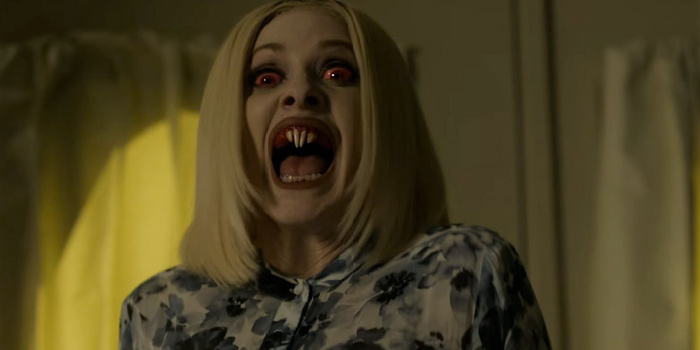 Image: Barbara Crampton hisses in her vampire form. She has shoulder-length blonde hair, red eyes, and rodent-like fangs. She stands in a white room with a demonic look on her face.