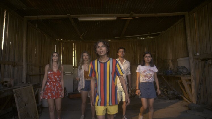 A still from Apps. Five people in a storage shed walk towards the camera looking curious and cautious.