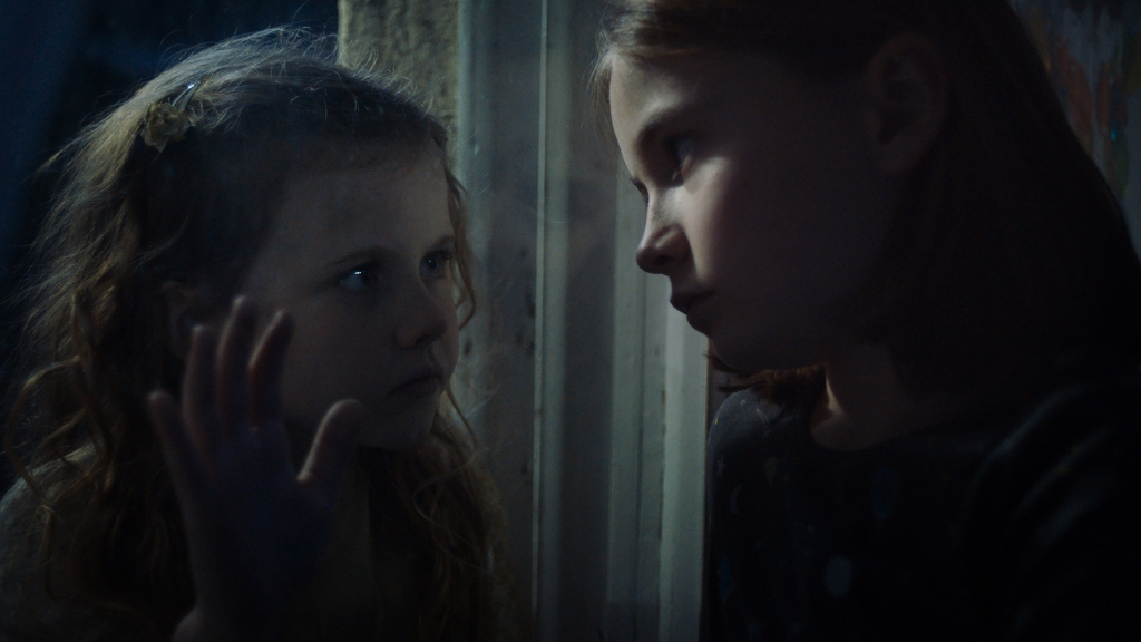 A still from Martyrs Lane. Two young girls face each other from opposite sides of a window.