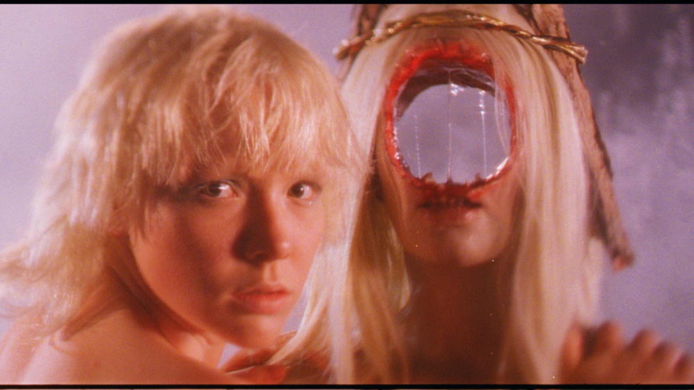 A still from After Blue (Dirty Paradise). A blonde woman turns to the camera and holds her hands on the shoulders of another blonde woman, who has a large bloody hole in the center of her face through which shows the background behind her.