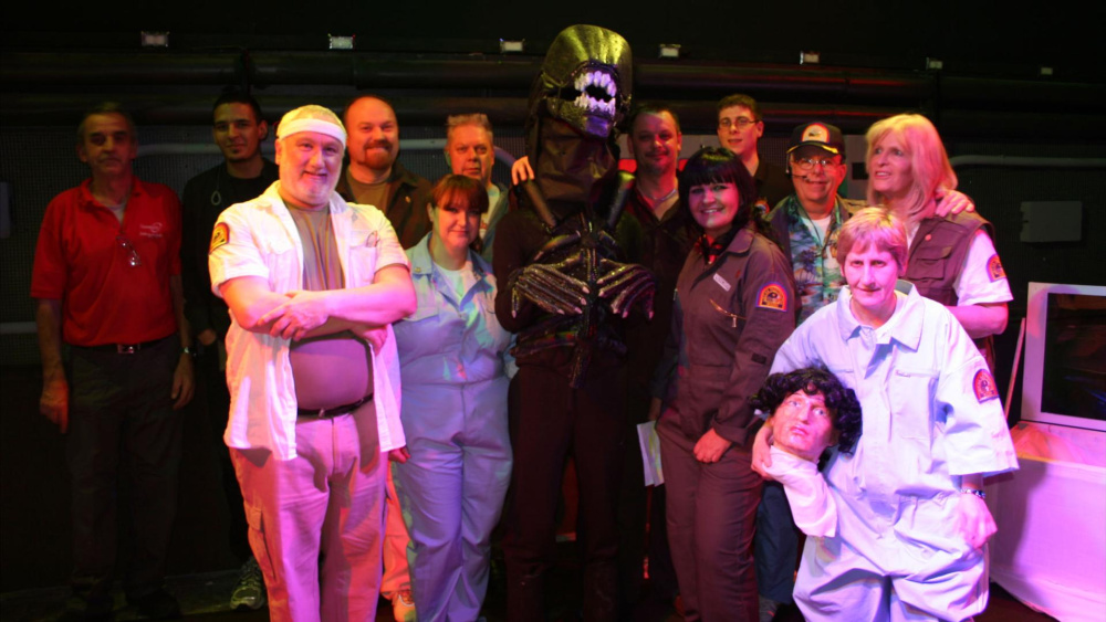 A still from Alien on Stage. A group of people stand in low-budget Alien costumes and smile at the camera.