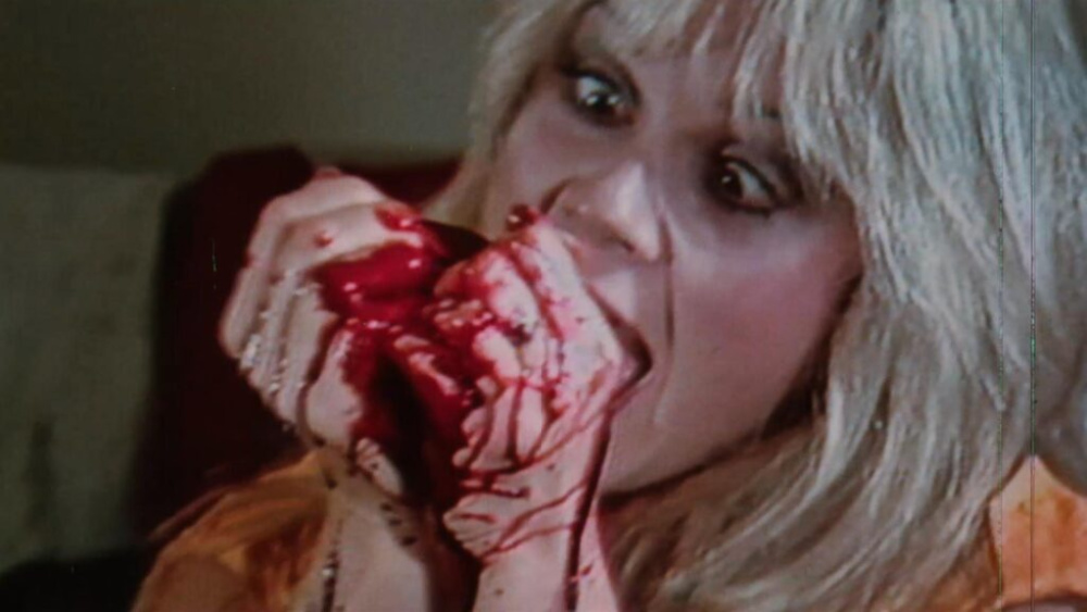 A still from Boardinghouse. A blonde woman holds something bloody in her hands and gnaws on it maniacally.