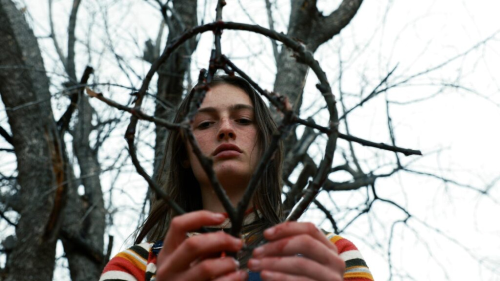 A still from Hellbender. A young woman standing under a leafless tree holds a pagan totem made of twigs in her hands and regards it stoically.