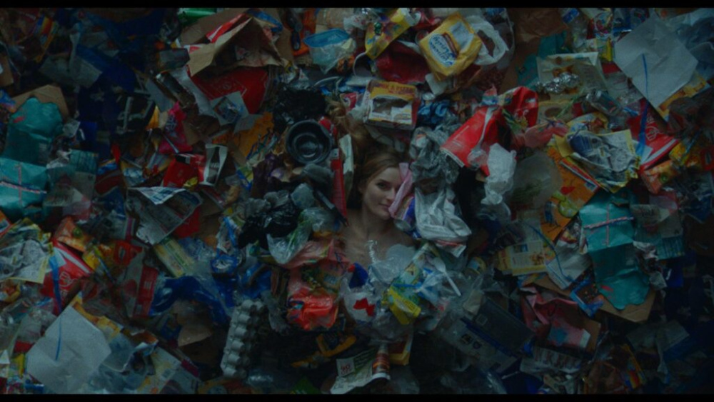 A still from Shapeless. A woman lies underneath a mountain of food wrappers and smiles enigmatically.