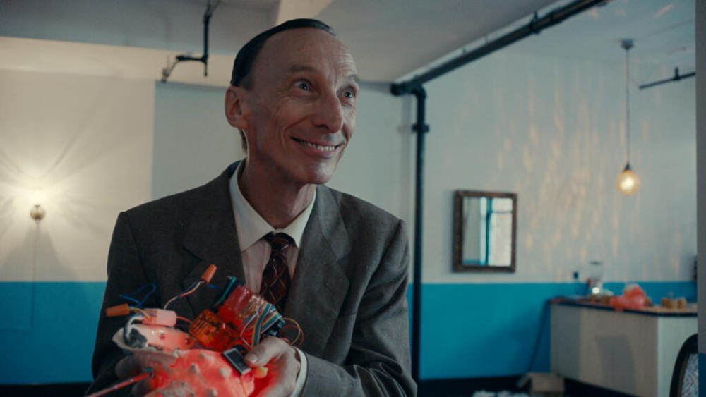 A still from Stanleyville. A man in a suit holds an odd device and smiles at someone off camera.