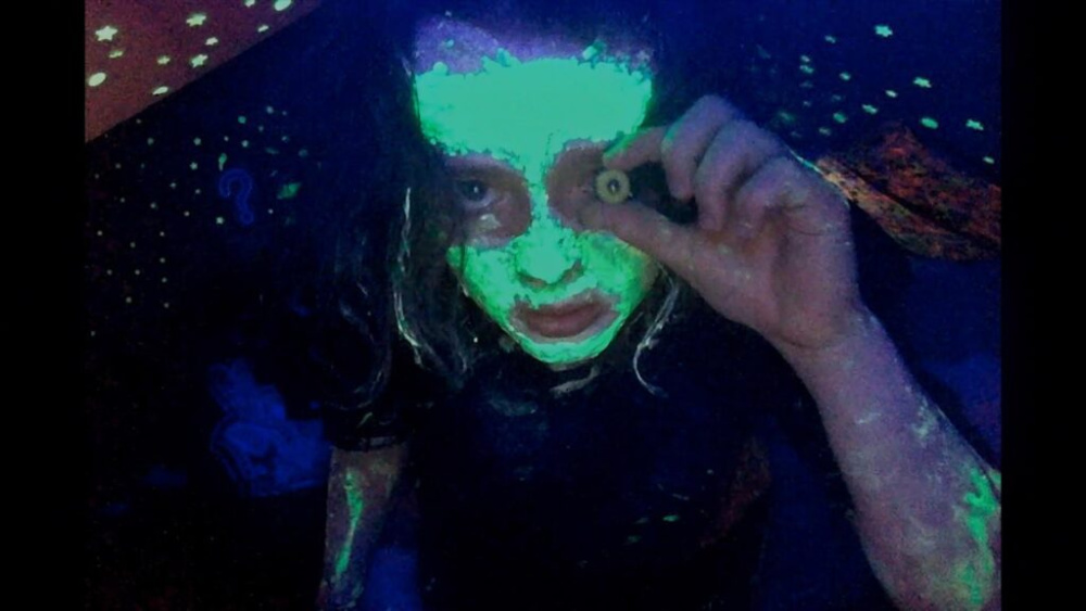 A still from We're All Going to the World's Fair. A young person with black light-reactive makeup all over their skin holds up a glass toy eye to their face and looks into the camera.